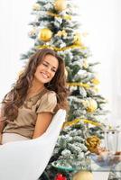 stående av den lyckliga unga kvinnan som sitter nära julgranen foto
