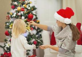 mor och baby dekorera julgran foto
