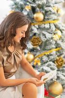 glad ung kvinna med vykort sitter nära julgran foto