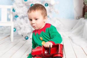 förvånad liten pojke på golvet med leksaksbil foto