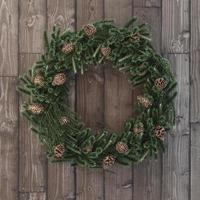 jul dekorativ krans med kottar på trä foto