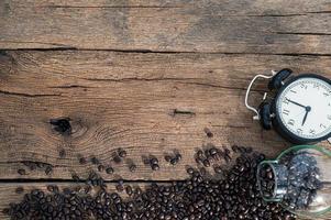 klocka och kaffebönor på skrivbordet
