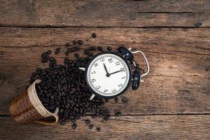 väckarklocka och kaffebönor på skrivbordet