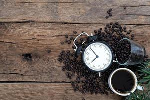 väckarklocka, en mugg kaffe och kaffebönor på skrivbordet