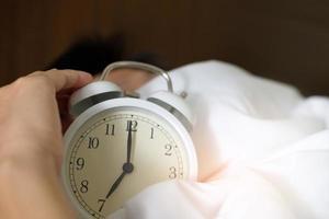 handen under filten med en väckarklocka foto