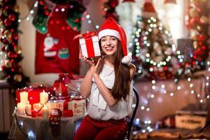 ung kvinna med nuvarande låda på jul foto