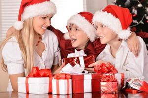 mamma och barn i santa hattar foto