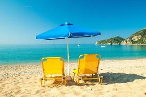 solstolar och paraply på den vackra stranden, Korfu, Grekland foto