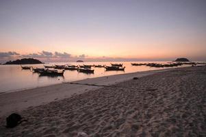 Longtail lokal båt på stranden vid solnedgången. foto