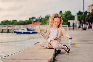 barnflicka som leker med leksakfågeln vid havet
