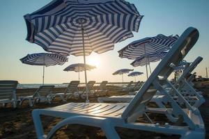 strand med paraplyer och solstolar