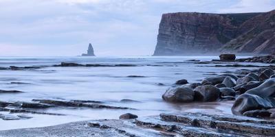 vacker marinmålning av stenar och havet vid solnedgången. sten nål.
