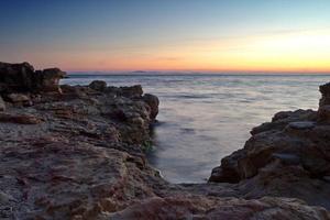 stenig strand vid solnedgången