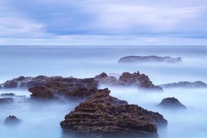 havslandskap av lättnadsstenar i de rörliga vågorna. foto