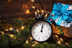 julgran, gåvor, lampor och klocka över träväggen foto