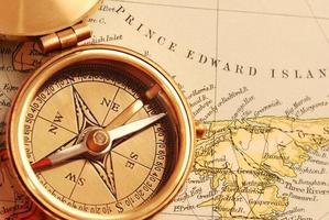 antik mässingskompass över gammal kanadensisk karta foto