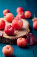 röda äpplen och blad träblå, turkos bakgrund foto