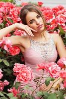 vacker kvinna sitter i buske med rosa rosor