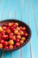 lergodsskål med saftiga körsbär på rustikt träturkosbord