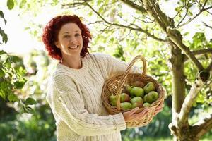 kvinna som plockar äpplen i trädgården