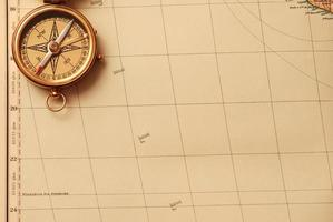 antik mässingskompass över gammal karta foto