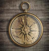 gammal mässingskompass på träbordsikt foto