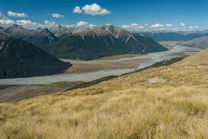 gräsbevuxna sluttningar ovanför Waimakariri-floden foto