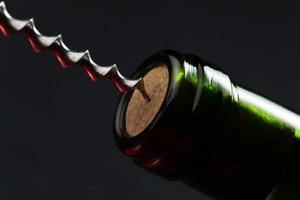 rött vinflaska och korkskruv foto
