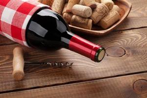 rött vinflaska, skål med korkar och korkskruv