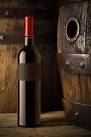 stilleben med vinflaskor, glas och ekfat. foto