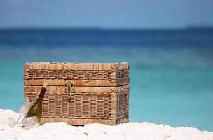 picknick korg på en strand med havet i bakgrunden foto