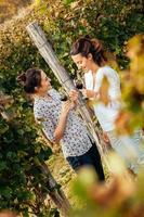 två unga kvinnor som dricker vin