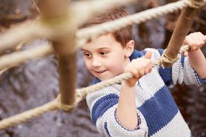 pojke som korsar ström på repbro på aktivitetscenter foto