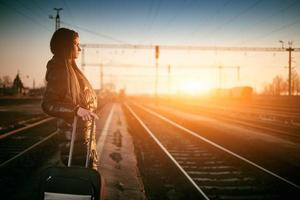 ung kvinnlig resenär med bagage som väntar med tågspår