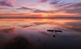 rött solnedgång vått strandkors
