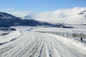snöig och isig väg med vulkaniska berg på vintern