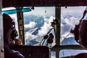 Visa kasta helikopter cockpit flyger på hög höjd bergspass
