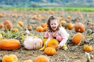liten unge flicka med mycket pumpor på fältet foto