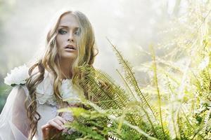 vacker blond kvinna bredvid ormbunken