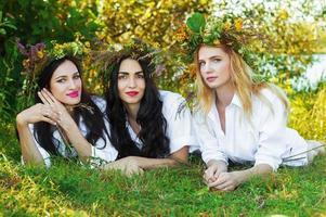 tre charmiga kvinna som ligger på gräset med blommakrans