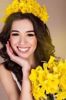 glad leende flicka med gula blommor foto