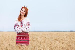 rödhårig tjej i nationella ukrainska kläder på vetefältet.