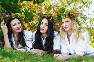 tre charmiga kvinna som ligger på gräset