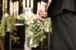 sorg - man med vita rosor vid urnerbegravning