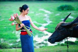 thailändska forntida unga kvinnor med buffel på landsbygden