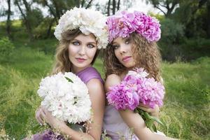 två tjejer med rosa pionkrans