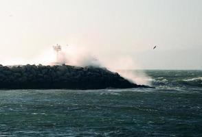 kraftfull våg som kraschar över vågbrytaren i Kalifornien foto