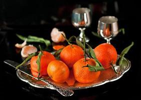 stilleben av färska mandariner med löv på en bricka