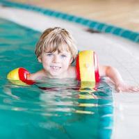 liten pojke med simmar som lär sig simma inomhuspool