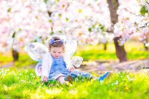 liten flicka i blommande trädgård